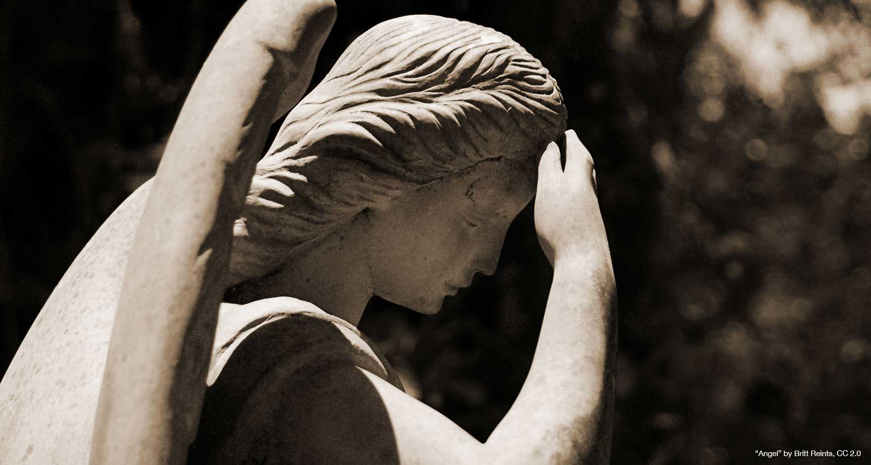 Close up of a statue of an angel with its hand to its forhead