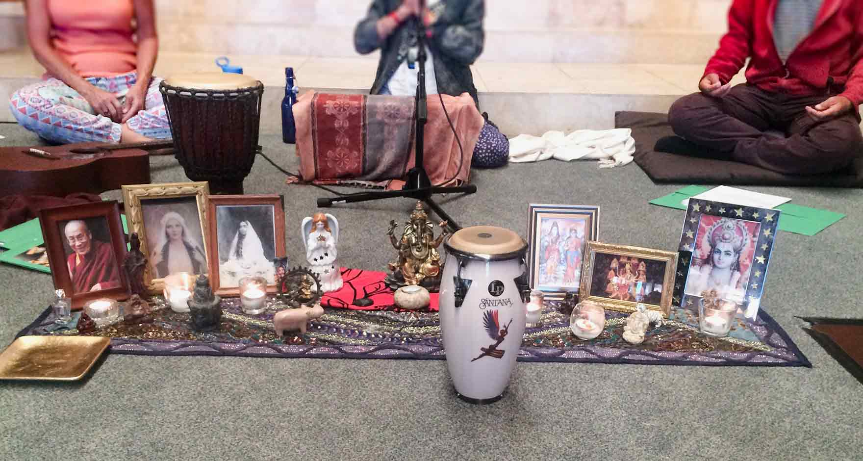 kirtan altar for the music and chants of Kirtan. The altar has framed photos and small statues on sitting on a sari