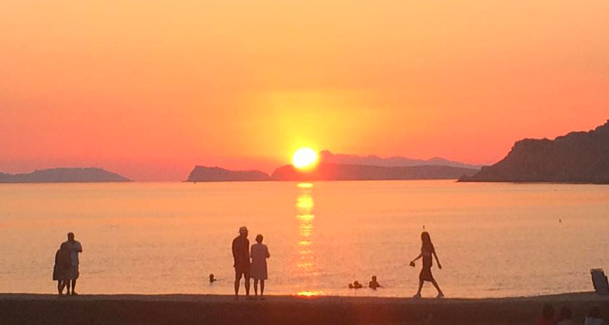 Sunset at Arillas Beach on Corfu, Greece with silhouette figures of 4 people