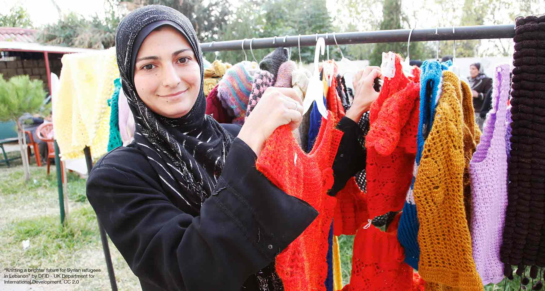Syrian refugee displaying her hand-knitted garments